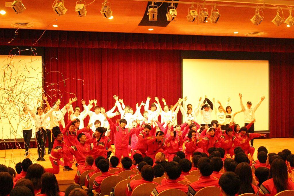 白黒の衣装の学生と赤いジャージの学生がステージに立つ様子の写真