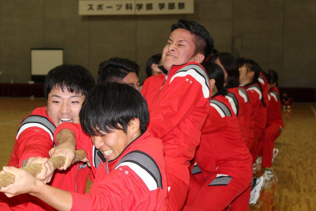 赤ジャージを着た学生が綱引きする様子の写真
