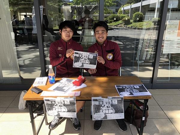 学生課前専用ブースでチラシを掲げる二人の学生の写真