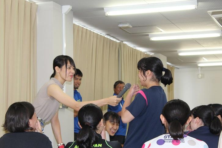 迫田さんが学生にマイクを向ける様子の写真