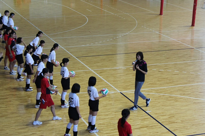 バレーボールを持って大林さんの話を聞く学生たちの写真